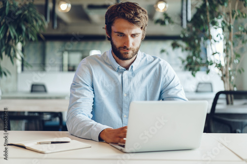 Businessman in shirt working on his laptop in an office. Open space office