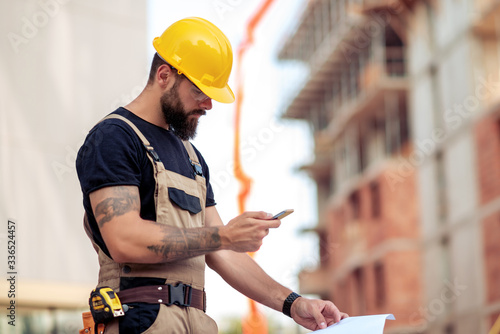 Fototapeta Engineer holding smart phone at construction site obraz