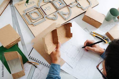 Obraz na plátně Box maker looking at box, drawing it's schematics