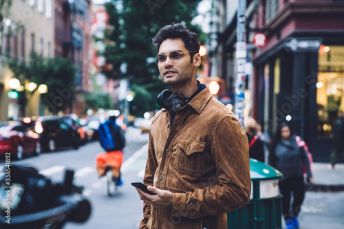 Confident ethnic young man with smartphone standing on crosswalk Fotobehang