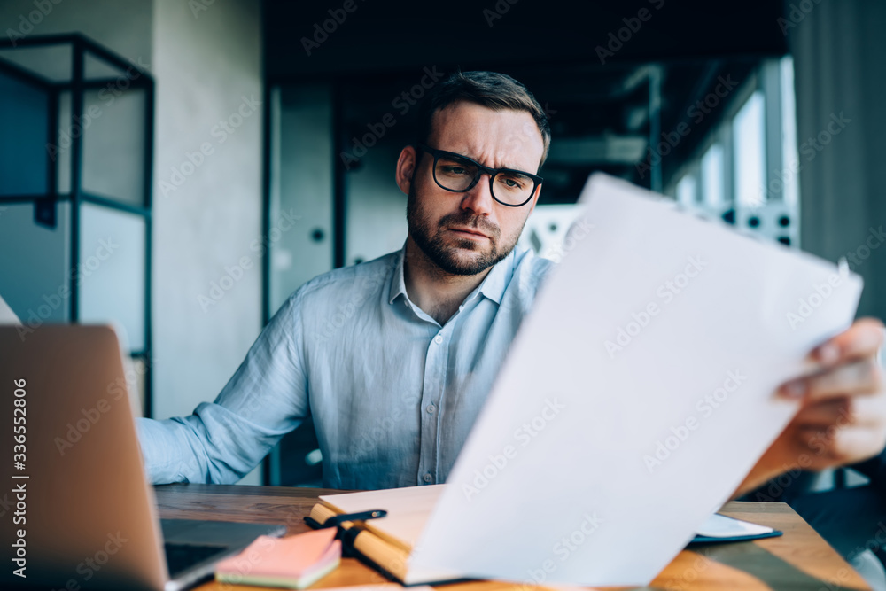 Fototapeta Businessman checking data in documents in office
