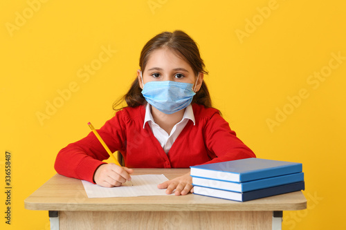 Cuadros en Lienzo Pupil in medical mask passing exam against color background