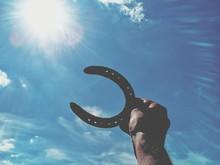 Cropped Hand Of Man Holding Horseshoe Against Blue Sky