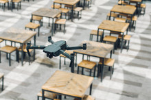 Close-up Of Drone Over Tables And Chairs