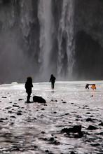 People Standing In Water Against Waterfall