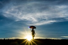 Silhouette Woman Under Umbrella Against Sun Streaming In Sky During Sunset