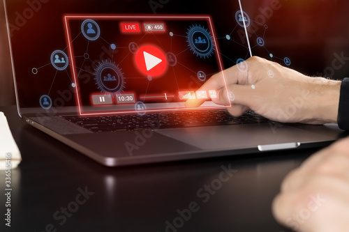 Fotografiet Attractive asian man using Laptop computer to watching live streaming video on social network