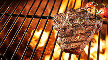 Two Portions Of Grilled Beef Steak On A BBQ