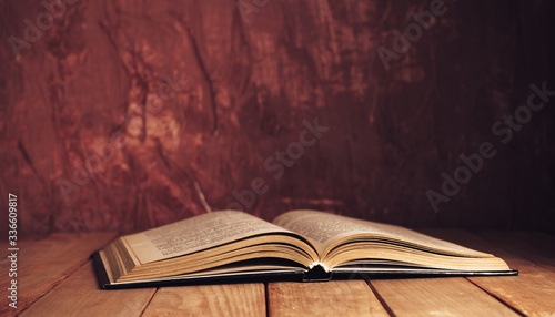 Photo Beautiful ancient open old book on a red  wooden table and dark-red wall background behind