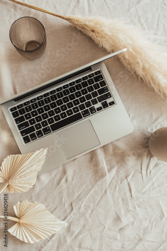 Obraz na plátne Home office desk workspace with laptop, reeds foliage, fan leaves on beige linen table cloth