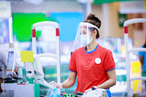 Fototapeta female supermarket cashier in medical protective mask and face shield working at supermarket obraz