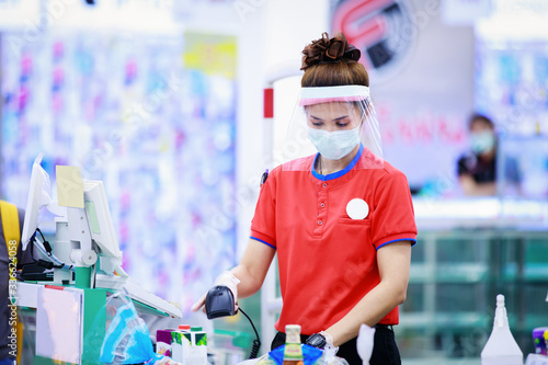 Fotografía female supermarket cashier in medical protective mask and face shield working at