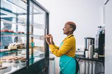 Cheerful Female Shop Assistant Opening Cake Display Fridge