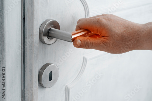 Fotografija Coronavirus safety tips concept: man open a door with a contaminated handle without protection
