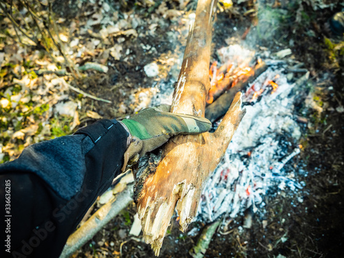 Obraz dokładanie drewna do ognia - fototapety do salonu