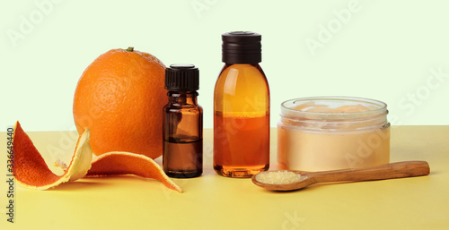 Fotografie, Obraz Orange essential oil in glass bottles on a yellow paper background, self-care an