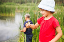 Child Boy Holding And Looking At The Fish. Grandpa And Grandson Fishing On The Lake