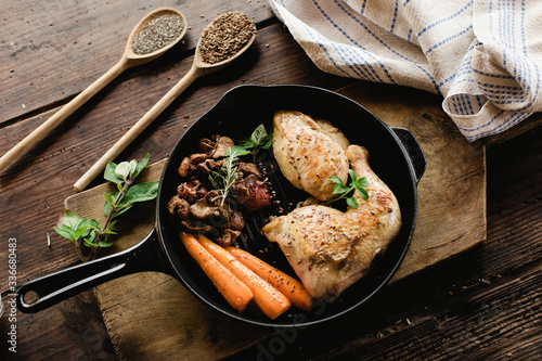Healthy cooked chicken pieces in a cast iron skillet. - 336680483