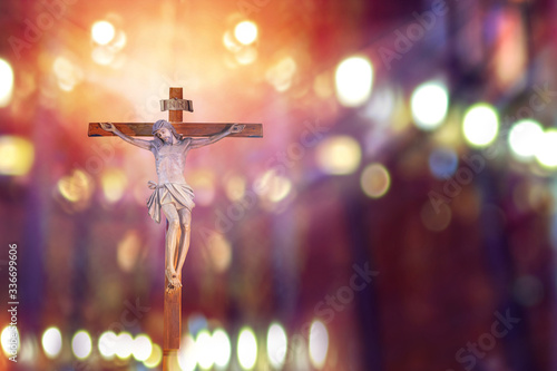 Fotografie, Obraz crucifix, jesus on the cross in church with ray of light from stained glass, eas