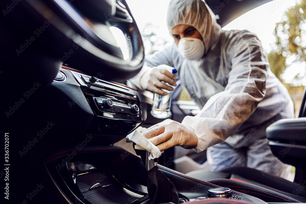 Fototapeta Man in protective suit with mask disinfecting inside car, wipe clean surfaces that are frequently touched, prevent infection of Covid-19 virus coronavirus,contamination of germs or bacteria.