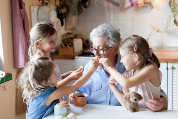 Kids treat grandmother at home. Happy family eating cookies in cozy kitchen. Senior woman and funny children tasting delicious food together, enjoying handmade pastries.