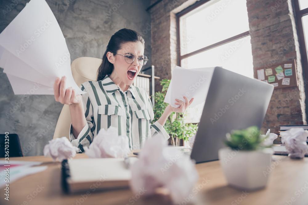Fototapeta Frustrated aggressive furious girl executive marketer work laptop prepare start-up development strategy presentation miss deadline hold paper scream sit desk in workplace workstation