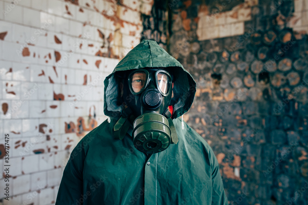 Fototapeta Dramatic portrait of a man wearing a gas mask in a ruined building.