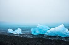 Blue Ice On The Jokulsarlon Ice Beach, Southern Iceland. Beautiful Coast Of Atlantic Ocean With Black Volcanic Sand