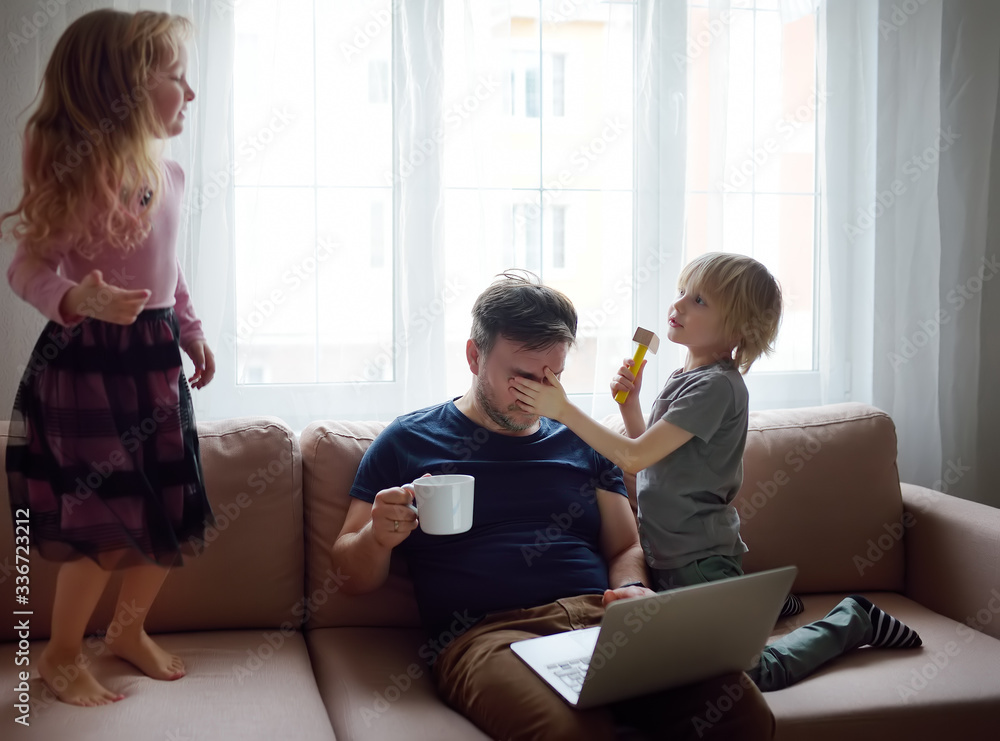 Fototapeta Tired father with his two kids during quarantine. Stay at home concept. Online working and household at the same time while quarantine.