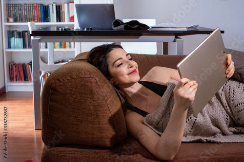Fotografía Ragazza mora guarda un film dal tablet sul suo divano