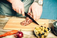 Male Hands Cut Jerky On A Kitchen Board