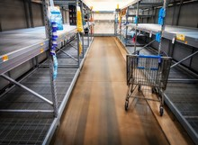 A View Down A Store Shopping Aisle Showing Empty Shelves And A Shopping Cart.