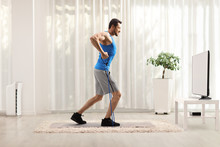 Fit Guy With A Resistance Band Exercising At Home In Front Of A Tv