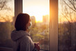canvas print picture - Woman near window at sunset in isolation at home for virus outbreak. Stay home concept