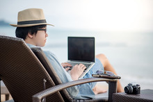 Asian Freelance Man In Casual Clothing Using Laptop Computer On Beach Chair Looking At The Sea. Remote Working From Anywhere In Summer Season.