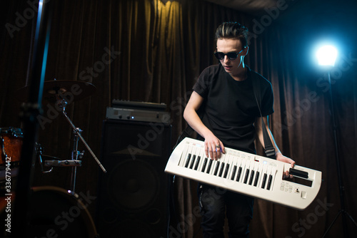 Man in sunglasses playing on electronic keyboard Wallpaper Mural