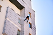 Rope Access Facade Maintenance. Worker Cleaning A Stone Exterior Of Apartment Building Facade.