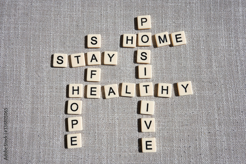 Photo Word game with crossword grids showing various words - stay, home, hope, healthy, safe, and positive - isolated on gray cotton background