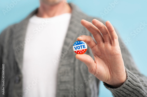 Photo Law abiding american citizen holding vote pin in hand