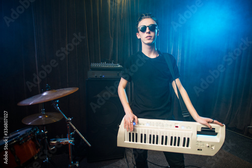Photo Man in sunglasses playing on electronic keyboard