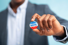 African Man Holding Vote Button On Blue Background
