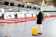 Man In Mask At Empty Airport At Check In In Coronavirus Quarantine Isolation, Returning Home, Flight Cancellation, Pandemic Infection Worldwide Spread, Travel Restrictions And Border Shutdown