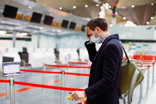 Man In Mask At Empty Airport At Check In In Coronavirus Quarantine Isolation, Waiting For Departure, Tourism Industry Crisis, Pandemic Infection Spread, Travel Restrictions And Border Shutdown