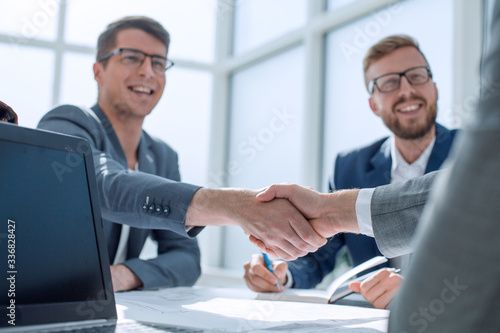 Obraz close up. business people shaking hands at a meeting in the office - fototapety do salonu