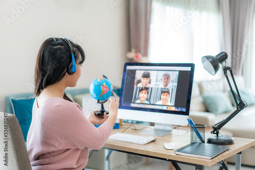 Fotografie, Obraz Asian woman teacher teaching geography via video conference e-learning and cheerful elementary school student looking at globe, Homeschooling and distance learning ,online ,education and internet