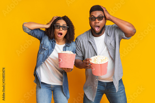 Fototapeta Shocked African Couple Holding Popcorn And Looking At Camera obraz