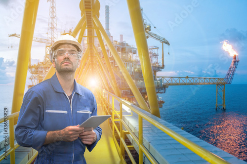 Fotografiet Caucasian man engineer staff worker with tablet in hand and offshore rig background concept
