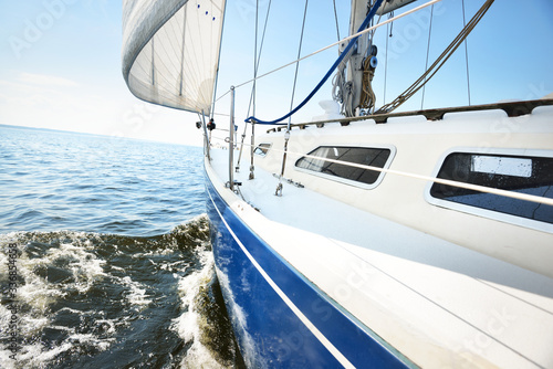 Fototapety, obrazy: White yacht sailing on a sunny summer day. Close-up view from the deck to the bow and sails. Waves and water splashes. Clear blue sky. Baltic sea, Sweden