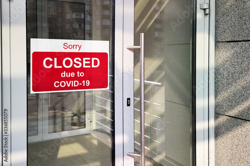 Fototapeta Business center closed due to COVID-19 coronavirus, sign with sorry in door window. Stores, restaurants, offices, other public places temporarily closed obraz