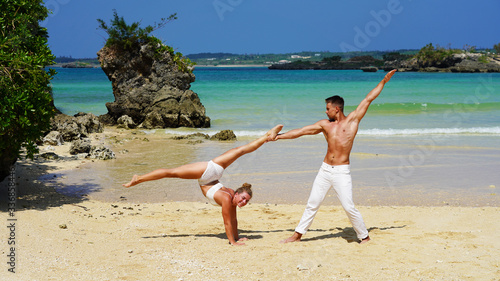 a pair of young flexible acrobats on the ocean posing on the beach Canvas Print